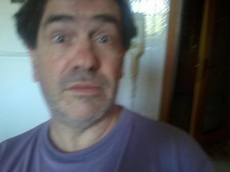 Giulio Mozzi fotografato dal postino (che tiene la macchina fotografica nella sinistra; mentre con la destra regge una precaria pila di plichi contenenti - si presume - opere letterarie dattiloscritte).
